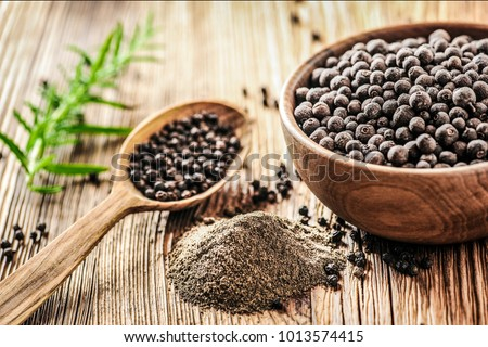 Black pepper in bow on wooden table. Pile of ground black pepper. #1013574415