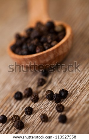black pepper in wooden spoon on rustic wooden background