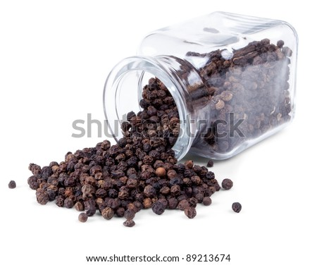 Black pepper is scattered on a white background from glass bottle