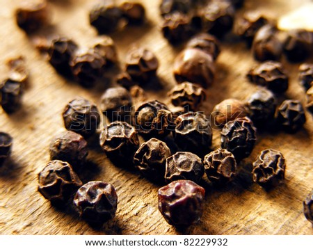 Black pepper on wood background