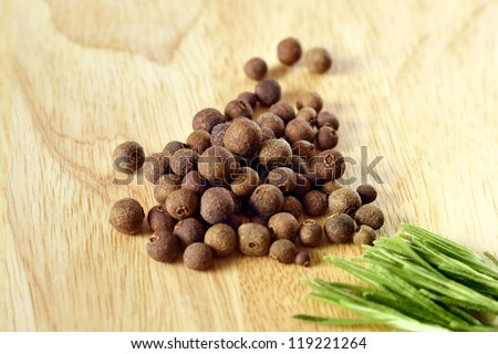 Black pepper on wooden background and green rosemary