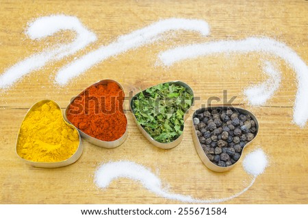 Black pepper, paprika, curry and basil in heart shaped containers on a wooden table sprayed with salt