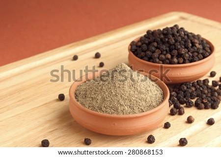 Black pepper powder and black pepper in terracotta pots on wooden plank