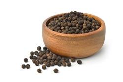 Black peppercorns (Black pepper) in wooden bowl isolated on white background.