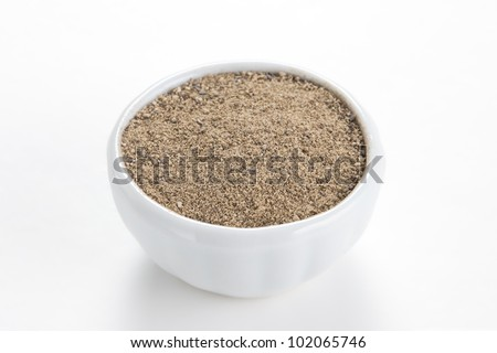Black peppercorns ground (Piper nigrum) in a white bowl on white background. Used as a spice in cuisines all over the world. The plant is also used in medicine.