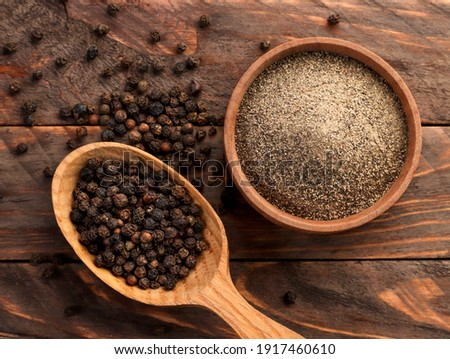 Black peppercorns in a spoon and black ground pepper in a plate close-up on a wooden background. Top view Stock photo ©