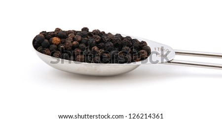 Black peppercorns measured in a metal tablespoon, isolated on a white background