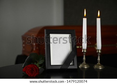 Black photo frame with burning candles and red rose on table in funeral home