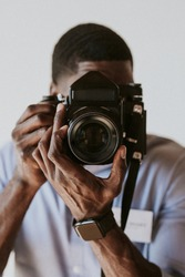 Black photographer capturing a picture with a retro film camera