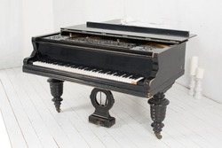 Black piano and two candles in a light room with white walls and floors