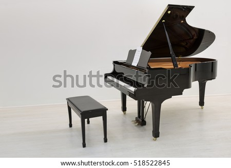 Black piano is ready to play in a white room