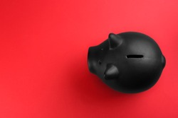 Black piggy bank on red background, top view. Space for text