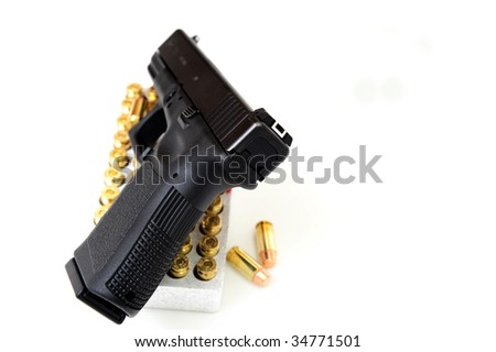 Black pistol also known as a handgun on a white background with a box of copper jacketed bullets under the gun.