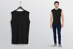 Black plan sleeveless shirt on a man male model in black denim jeans pant, isolated, mockup. Hanging black blank sleeveless shirt shirt, against empty wall.