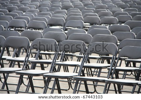 Black plastic chairs set for an outdoor event.
