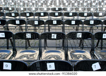 Black plastic chairs set for an outdoor event with numbers on back