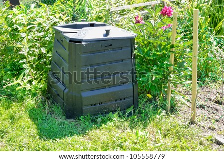 Black plastic compost bin in allotment garden