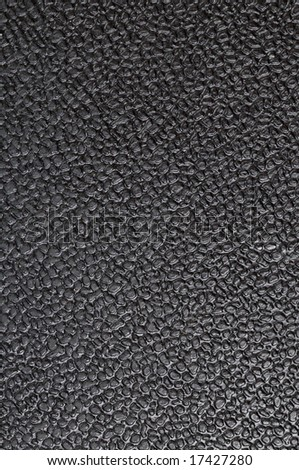 Black plastic from office chair. Close-up. Texture. Dusty and dirty.