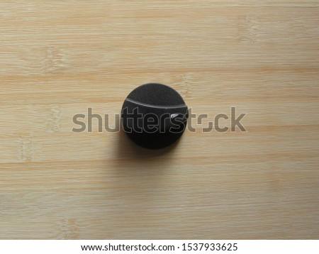 Black plastic On Off Gas stove knob kept on wooden table