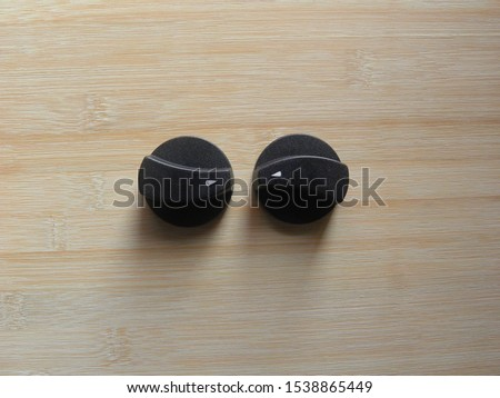 Black plastic On Off Gas stove knobs kept on wooden table