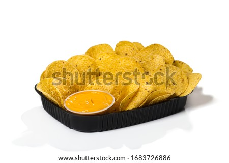 Black plastic tray of round yellow nachos with melted cheese dip on white background isolated Foto stock ©