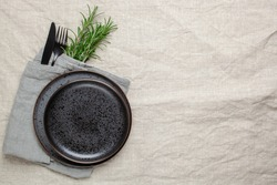 Black plate, cutlery and napkin with a sprig of rosemary on textile table. Top view. Table setting.