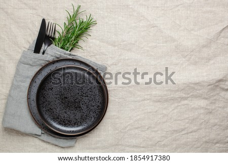 Black plate, cutlery and napkin with a sprig of rosemary on textile table. Top view. Table setting. Photo stock ©