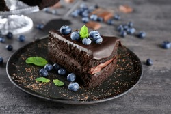 Black plate with delicious chocolate cake on grey background