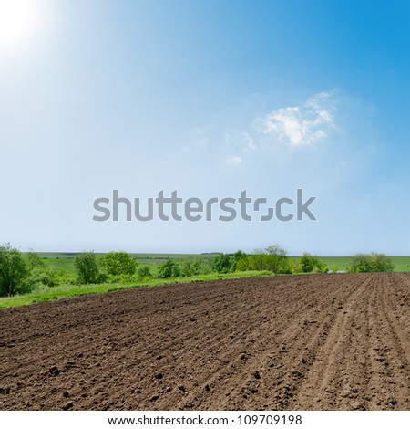 black ploughed field under deep blue sky with sun