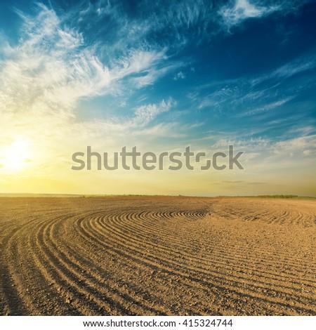 black plowed field in sunset #415324744