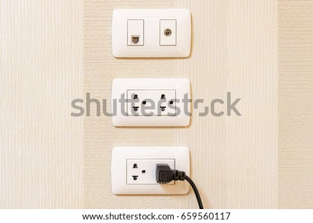Black plug inserted in a wall socket on background. Modern plug is plugged into the power lines with electric cord.  Difference device for connecting electrical appliances