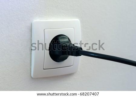 Black plug plugged in a socket. - stock photo