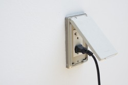 Black plug plugged in a socket with cover for outdoor