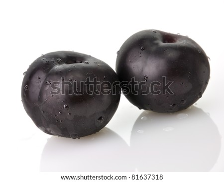 black plums , close up on white background