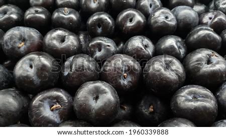 black plums on supermarket display