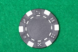 black poker chip on the green casino table