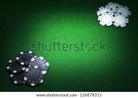 Black poker chips versus White poker Chips on green casino felt with copy space between. Gambling concept