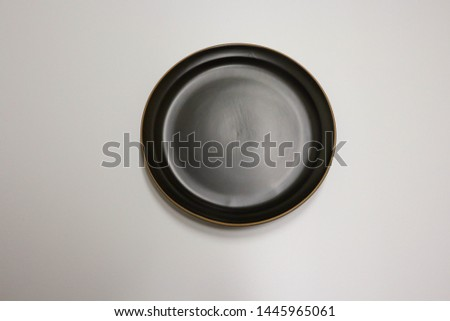 Black porcelain dish. It is a flat dish.