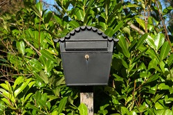 Black post box with key and green leaves