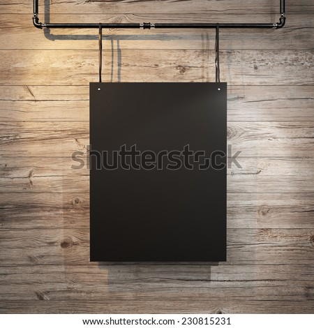 Black poster hanging on leather belt on wood background
