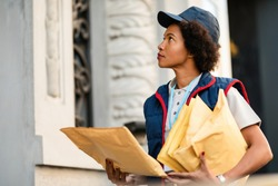 Black postwoman delivering mail in residential district.