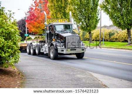 Black powerful big rig industrial semi truck with step down semi trailer and sign on the cab roof for transporting oversize load running on the local road with autumn trees on the side #1576423123
