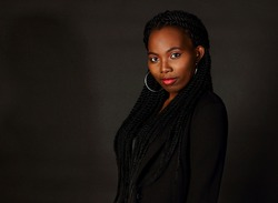 Black  pretty girl with dreads in dark classic jacket in studio, young Afro woman with pink lips and dreadlocks looking at camera