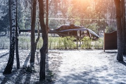 Black private modern luxury helicopter standing on grass field near forest at country rural landscape. Rich buiness lifestyle travel. VIP aero taxi service .Early morning departure