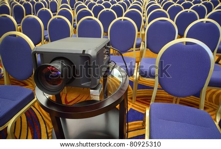 Black projector on background of rows of yellow-blue chairs in bright conference hall