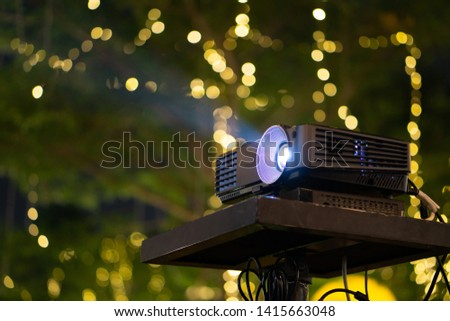 Black Projector on stand table ready for presentation in yellow bokeh background.