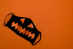 Black protective mask with orange eyes and mouth on an orange background.Halloween and covid-19 concept.Copy space for text, top view