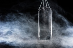 Black punching bag in empty room filled with smoke  isolated on black