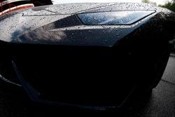 Black racing car. Wet hood, bumper, headlight close-up with drops of water. Close-up.