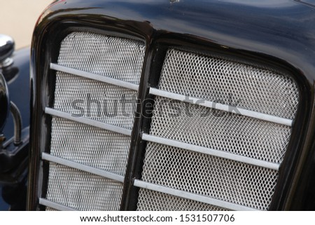 Black radiator grille on a car with chrome parts. #1531507706